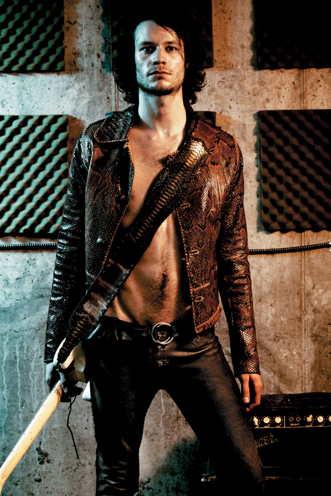 Male model wears hand-made a Lost Art™ Python Snakeskin Jacket, a Lost Art™ Leather Pants, a Lost Art™ Leather Belt and a Lost Art™ Snakeskin Guitar strap